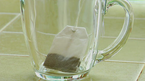 Boiling water poured over a tea bag in a clear glass... Stock Video Footage