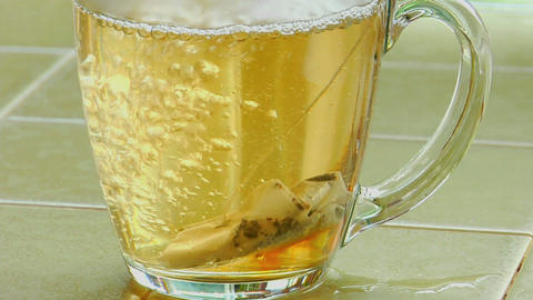 Boiling water poured over a tea bag in a clear glass coffee cup Footage