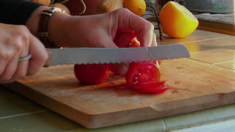 A woman chef slices fresh tomatoes on a wooden cutting board Stock Video Footage
