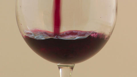 A slow motion pour of red wine into a wine glass Footage
