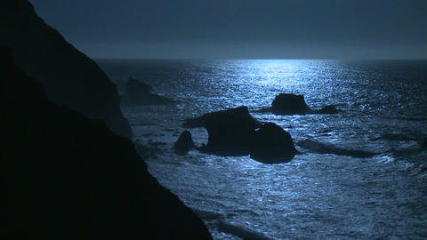 Surf rolls into the Big Sur Coastline of California under a full moon effect Footage