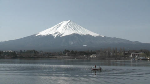 Mt. Fuji rises above Lake Kawaguchi and a small sport fishing boat, Japan Footage