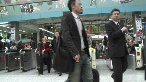 Commuters pass through the turnstiles in Ueno station during rush hour in Tokyo, Japan Footage