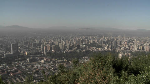 Pan across the smog filled city of Santiago to the Andes Mountains, Chile Live Action