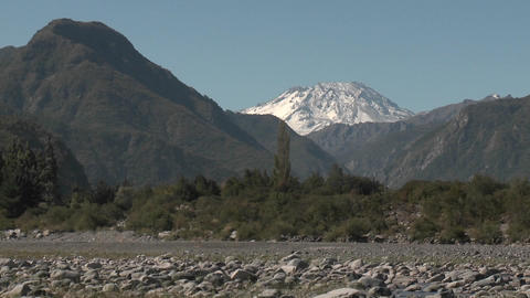Slow move out of a dry river bed and snow capped peak in the Andes above Talca, Chile Footage