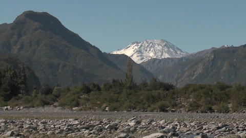 Slow move out of a dry river bed and snow capped peak in... Stock Video Footage