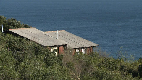 A cabin sits on a bluff overlooking the ocean near... Stock Video Footage