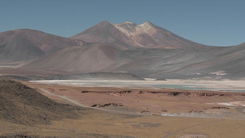 A truck passes through the colorful altiplano scenery surrounding the Salar de Laco in the altiplano Footage