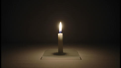 A small candle burns in a dark room Footage
