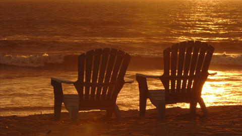 Waves roll into beach front Adirondack chairs Stock Video Footage