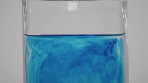 Blue dye diffuses through a glass of water Stock Video Footage