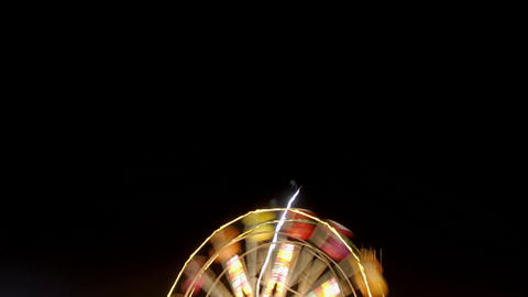 Fireworks explode over a Ferris wheel in time lapse Stock Video Footage