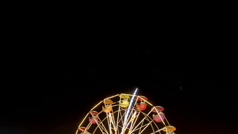 Fireworks explode over a Ferris wheel in time lapse Footage