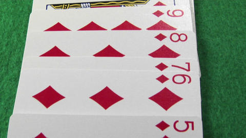 The camera moves across a deck of cards laid out on a casino table Footage