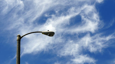 Time-lapse of clouds blowing by a light pole Stock Video Footage