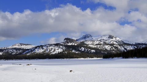 Time-lapse of clouds blowing over frozen lake and mountains Stock Video Footage
