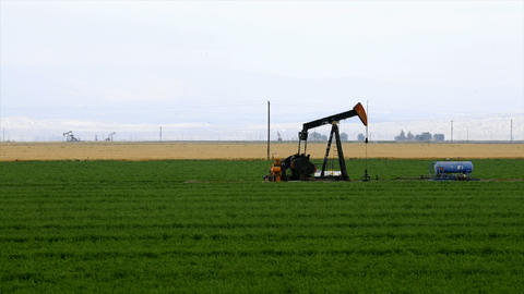 Time lapse of an oil well pumping in the middle of a crop... Stock Video Footage