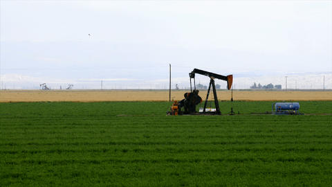 Time lapse of an oil well pumping in the middle of a crop field Footage