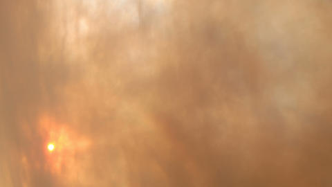 Time lapse of smoke clouds blowing in front of the sun Stock Video Footage