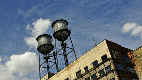 Time-lapse of clouds blowing above a building with two water towers on top Footage