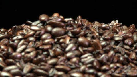 Rack focus of roasted coffee beans in a pile Footage