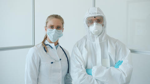 Portrait of man and woman doctors in protective uniform standing in clinic Live Action