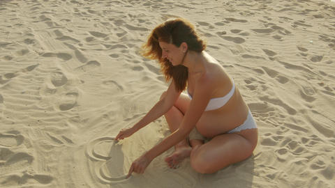 Pregnant woman sitting on the sea sand draws a heart symbol on the sand Live Action