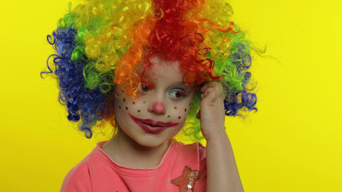 Little child girl clown in colorful wig tells something interesting, having fun Live Action