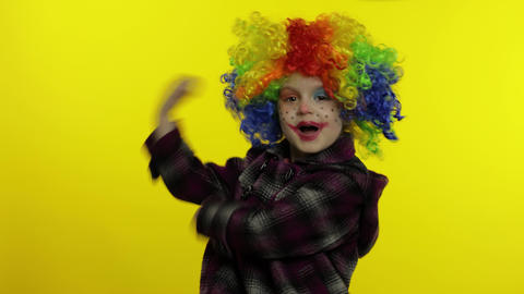 Little child girl clown in colorful wig making silly faces, having fun, smiling Live Action