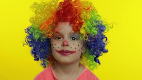 Little child girl clown in rainbow wig tells something interesting. Having fun Live Action