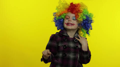 Little child girl clown in colorful wig making silly faces. Having fun, shows Live Action