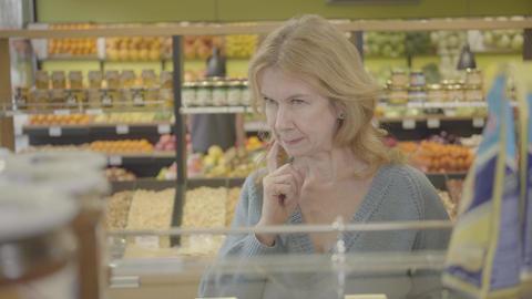 Portrait of confident adult Caucasian woman looking through shelves in Live Action