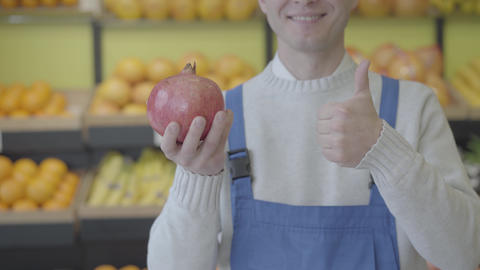 Cheerful unknown Caucasian man in blue workrobe holding pomegranate in hand and Live Action