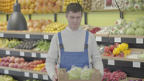 Portrait of adult Caucasian man holding box with fresh organic cabbages and Live Action