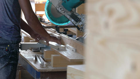 Contractor sawing wood plank with an electric saw machine inside a wood factory Live Action