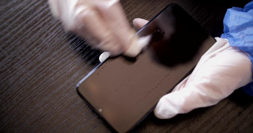 Young woman cleaning cellphone with gloves and face mask Live Action