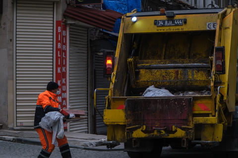 Street cleaner wearing face mask to protect from Corona virus (COVID-19) putting waste to garbage フォト
