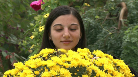 Teenager girl smelling flowers Footage