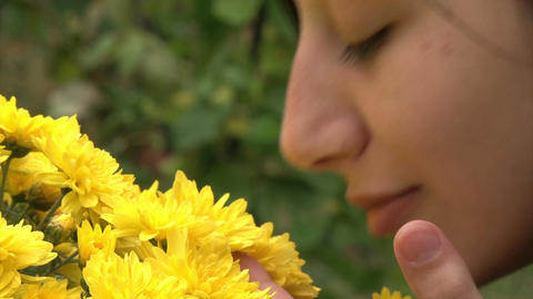 Teenager girl smelling flowers, Live Action
