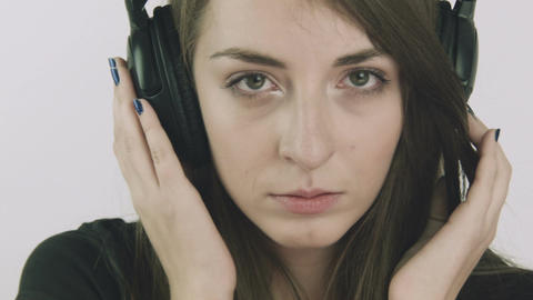 Attractive young sad woman listening to music on headphones Footage