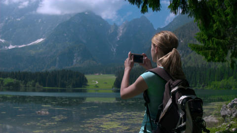 Mid shot - Young female hiker with a backpack taking photos with her phone Footage