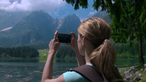Closeup - Young female hiker taking photos of a nature with her phone Footage