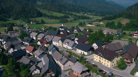 Aerial - Flying away from a small rural village beneath the Alpine mountain Live Action