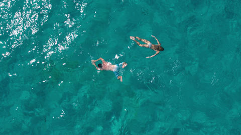 Aerial - Top down view of a couple with fit bodies swimming underwater Footage