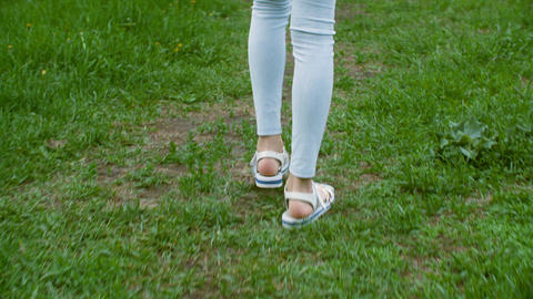 Teenager girl legs in blue leggings and sandals walking then running on grass Live Action