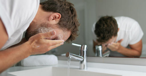 Man washing face with facial cleanser face wash soap in bathroom sink at home Live Action