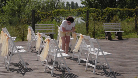 Woman decorator decorates chairs at the wedding registration Live Action