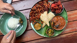 Meals served on banana leaf consists of fried chicken, curry seafood, canai and etc, a traditional Live Action
