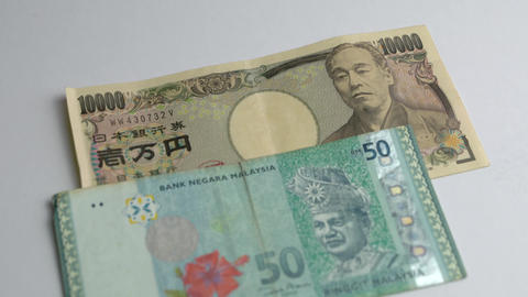 Japanese yen and Malaysia ringgit side by side on white background Live Action