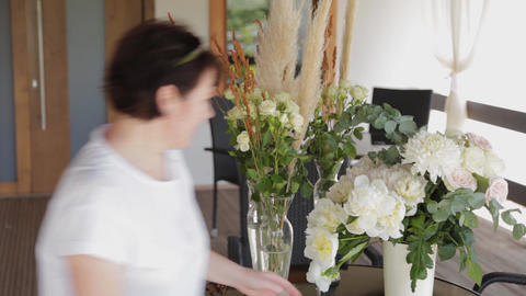 Wedding decorator decorates flowers on tables Live Action
